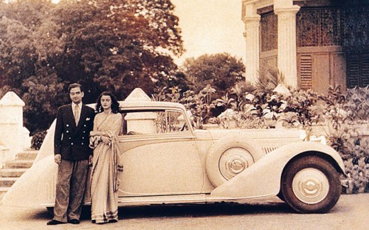Mahrani Gayatri Devi poses with an unidentified man next to a custom built Rolls-Royce in Jaipur